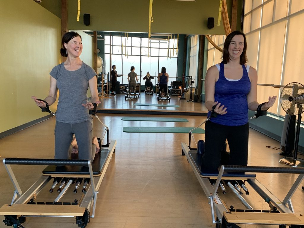 two women on pilates reformers