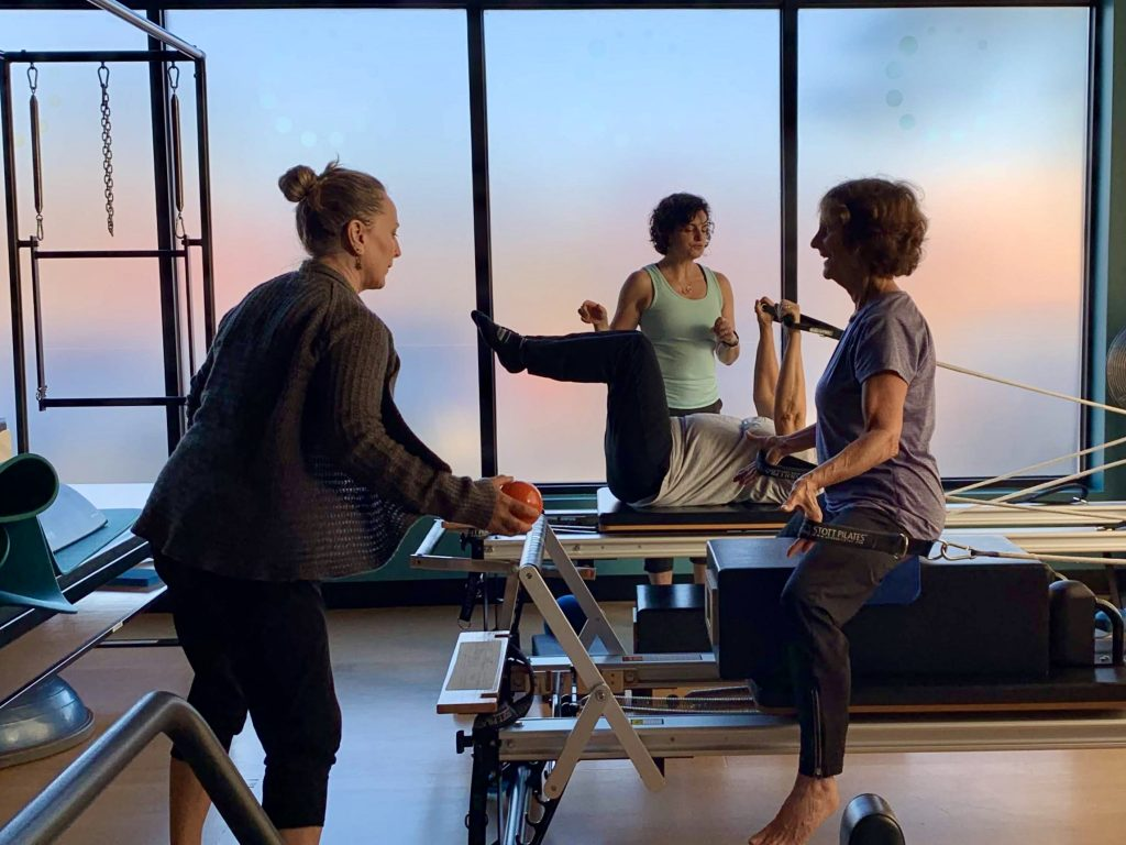 Light filtering into a Pilates studio while people work with trainers.