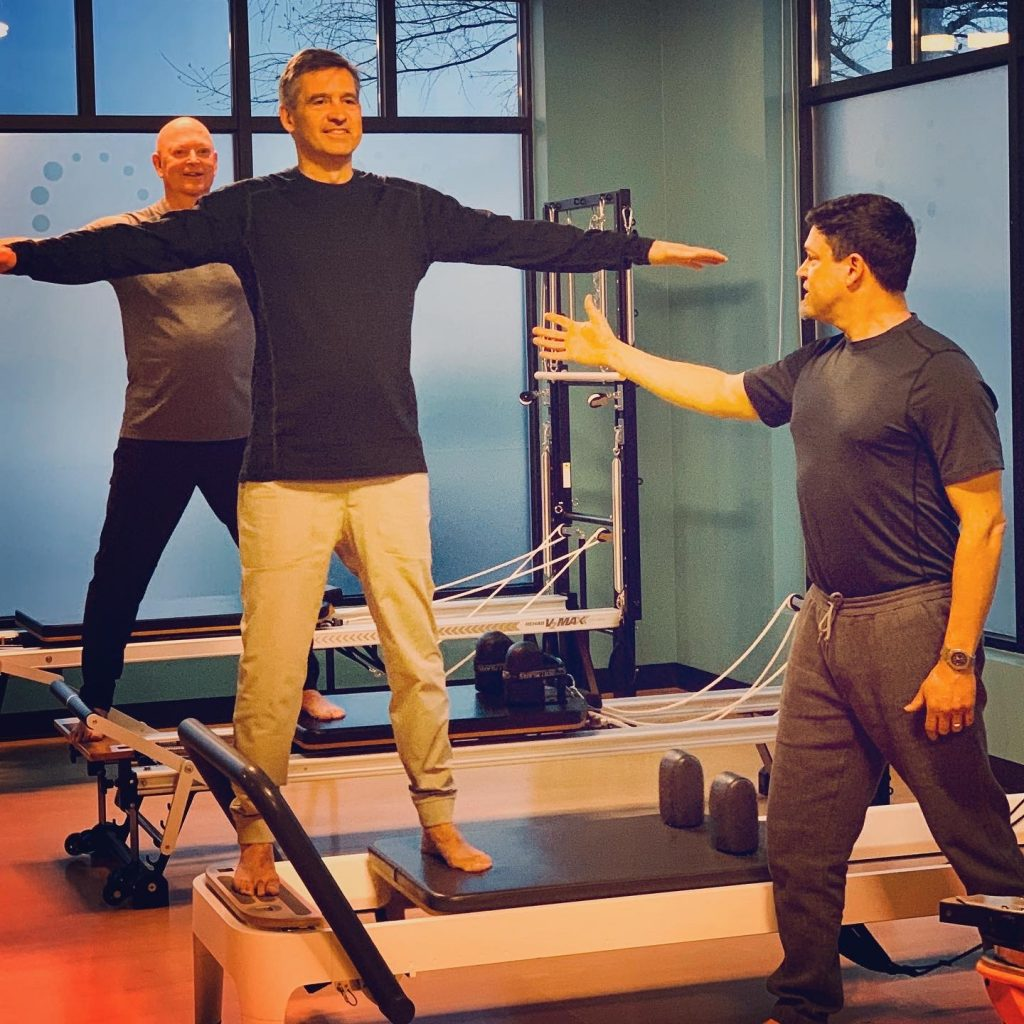 Two men working out with a trainer on the Pilates Reformer