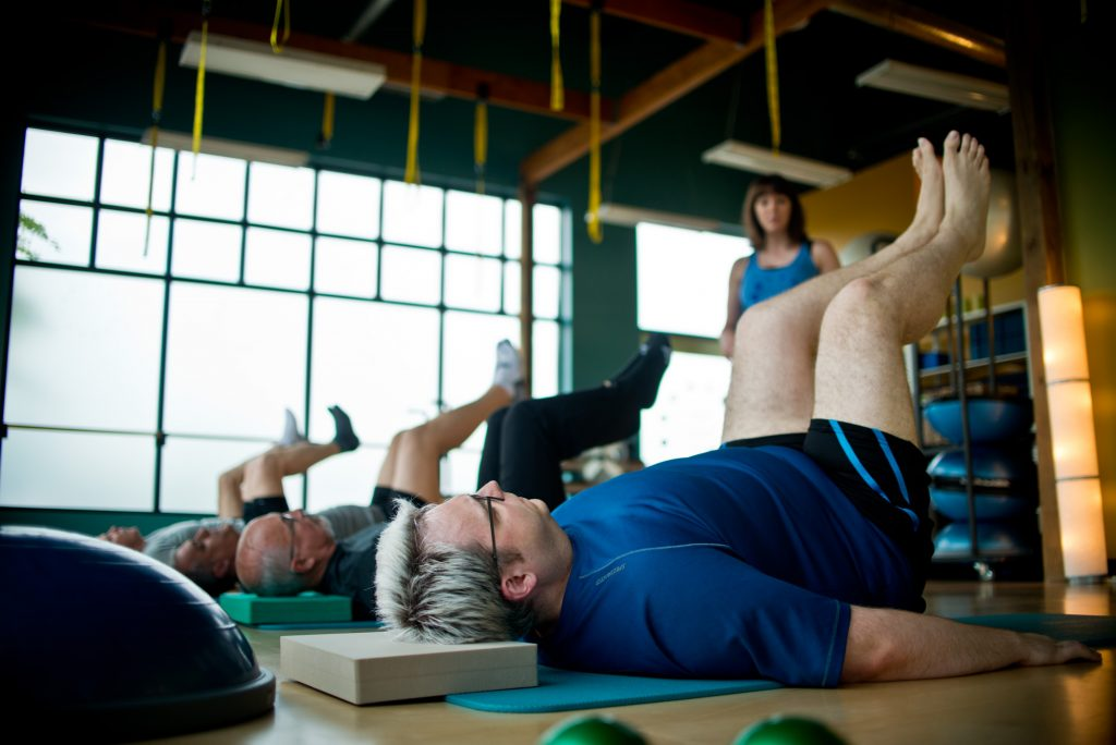 A group of men participating in a Pilates mat class