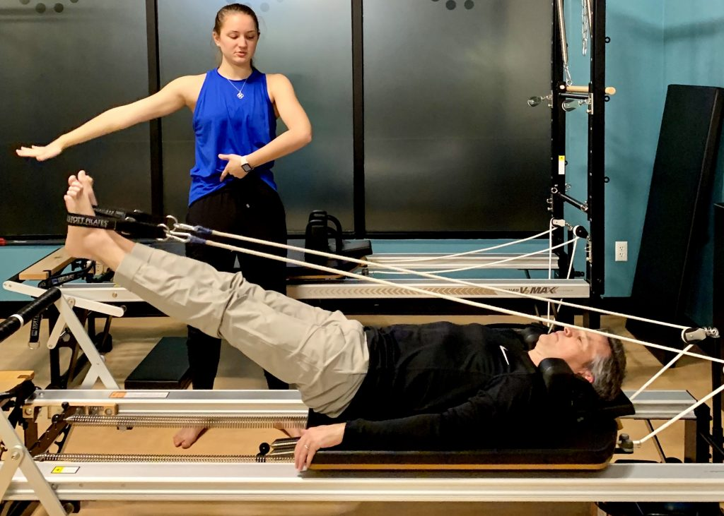 A man working out with a personal trainer on the Pilates Reformer
