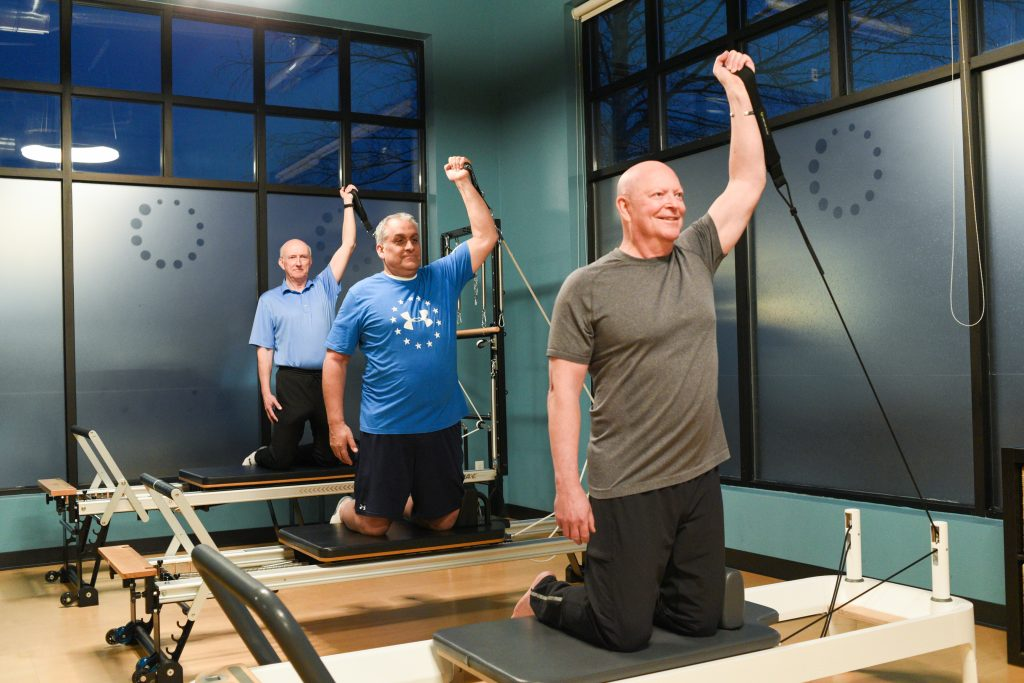 Three men doing an arm workout on the Pilates Reformer