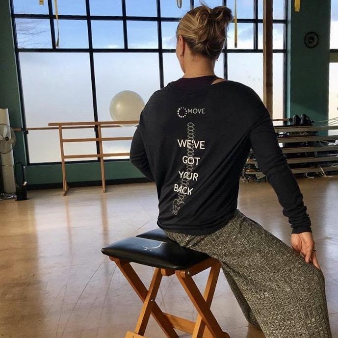 Gyrokinesis stool trainer wearing 'we've got your back' shirt