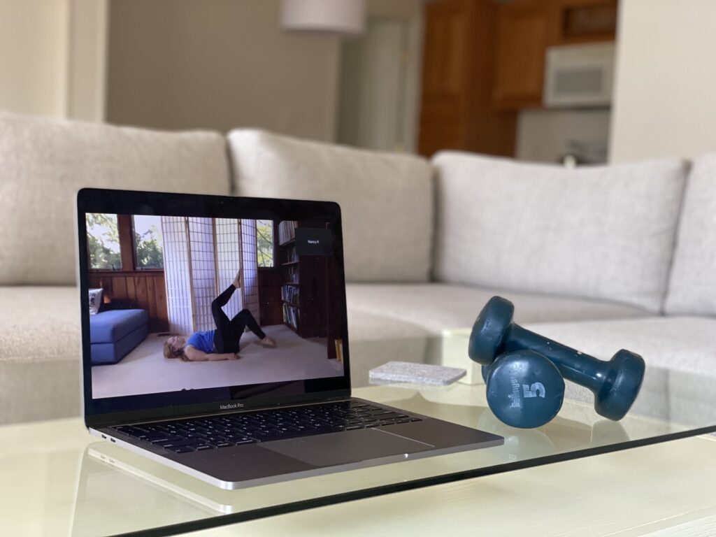Laptop displaying a MOVE Livestream class in someone's living room.