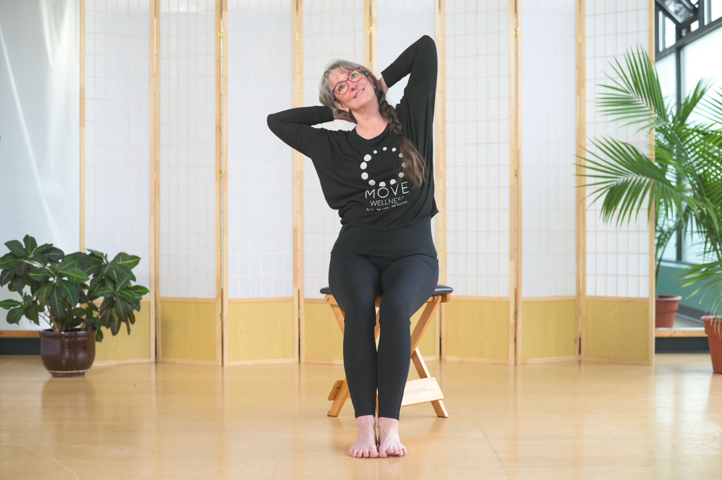 Pilates Trainer sitting on a stool doing stretches for sitters