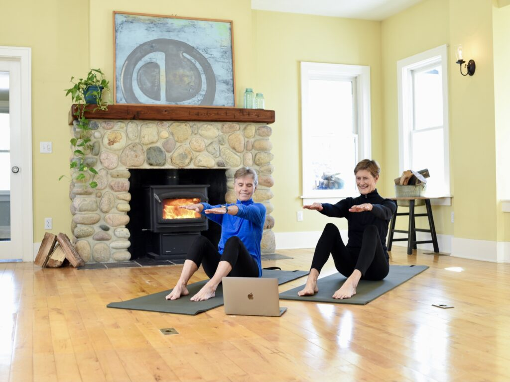 2 women doing online fitness classes on a mat in their living room