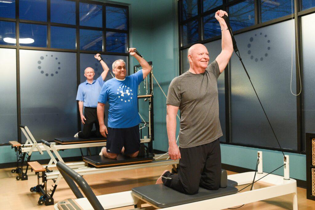 3 senior men doing Pilates Reformer arm exercises